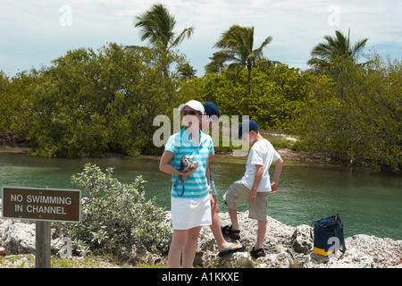 A woman and her son with video camera standing next to an inland waterway in the Florida Keys. - Stock Photo