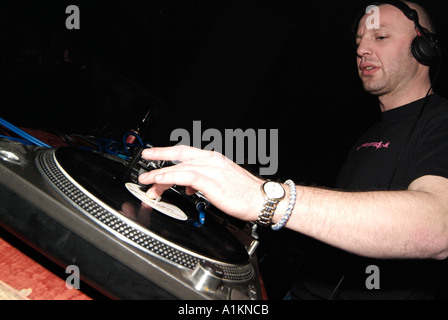 Club DJ Cutting in a Track on a Turntable Behind the Decks of a Nightclub - Stock Photo