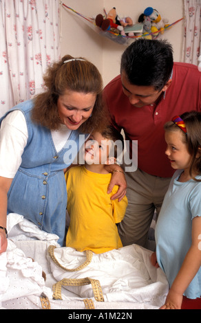 Happy Couple expecting twins showing young daughter and son Moses baskets for babies - Stock Photo