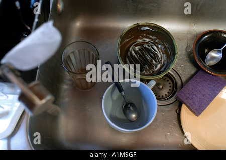 Dirty dishes in a dirty sink - Stock Photo
