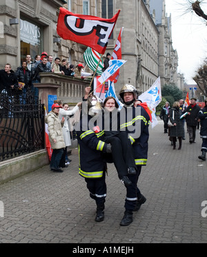April 14 2006, 2 firemen carrying a protester girl holding a flag, protest march against Bolkestein directive, Strasbourg, - Stock Photo