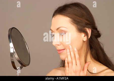 MR Attractive woman applies beauty cream on her face - Stock Photo