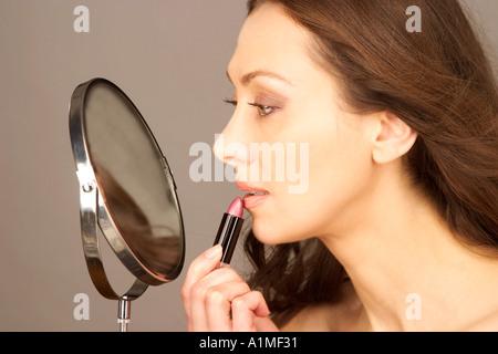MR Attractive woman applies lipstick - Stock Photo