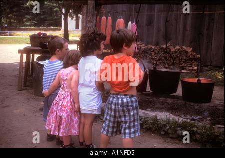 Young children watching wool dying demonstration at Old Sturbridge Village Sturbridge Massachusetts USA - Stock Photo