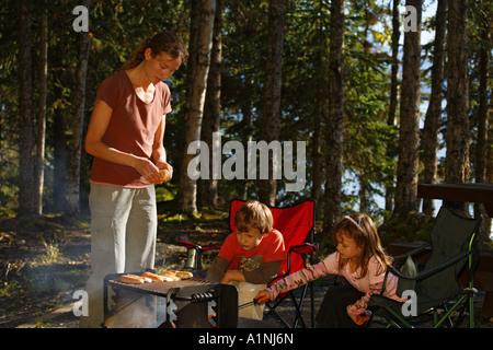Roasting hotdogs at family picnic at Trail Lake Campground Kenai Peninsula Chugach National Forest Alaska MR - Stock Photo