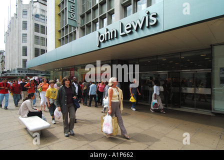 London City of Westminster Oxford Street shoppers John Lewis department store frontage entrance with lady seated - Stock Photo