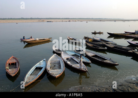 Boats on the holy river of Ganges in Varanasi in India - Stock Photo