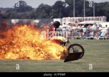 Stunt rider on motorcycle driving through burning tunnel made from straw bales soaked in petrol - Stock Photo