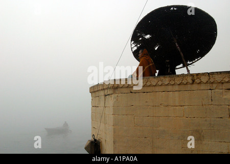 A man meditates on the bank of the holy river Ganges in the city of Varanasi in northern India - Stock Photo