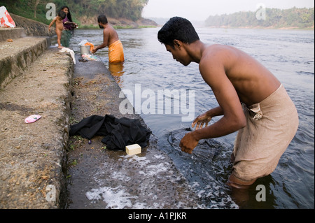A man and a family washing clothes in the river in Kerala India - Stock Photo
