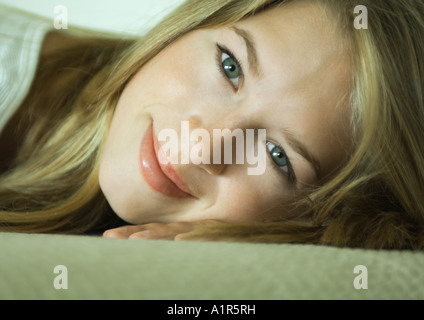 Young woman resting head on hand, smiling, close-up - Stock Photo