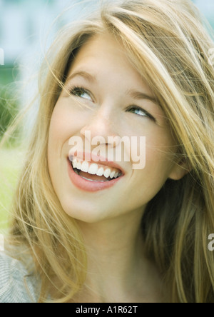 Young woman smiling and looking up, portrait - Stock Photo