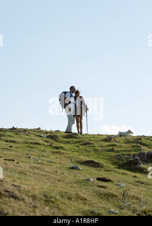Hikers in mountainous landscape - Stock Photo