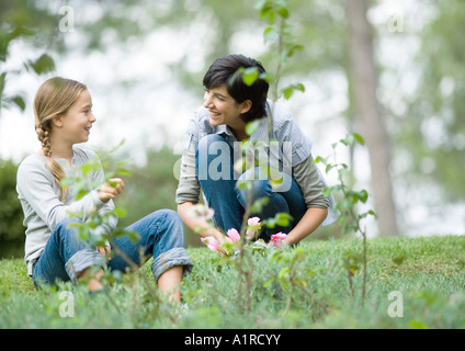 Mother and daughter doing yardwork, chatting - Stock Photo
