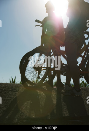 Mountain bikers standing by bikes, backlit - Stock Photo