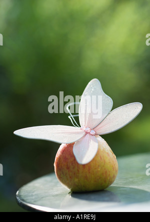 Fake butterfly on top of apple - Stock Photo