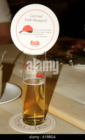 head on a drink typical Koelsch beer glass at Dom Frueh beerhall  Cologne Koeln North Rhine Westphalia Germany - Stock Photo