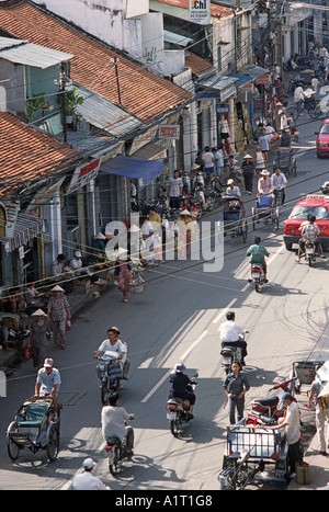 Street scene in central Ho Chi Minh City Saigon with pedestrians rickshaws motor cyclists street traders Vietnam - Stock Photo