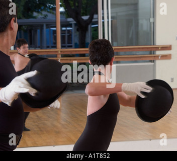 A Caucasian woman and hispanic man dancing in black and white gloves and holding bowler hats turned away from viewer - Stock Photo