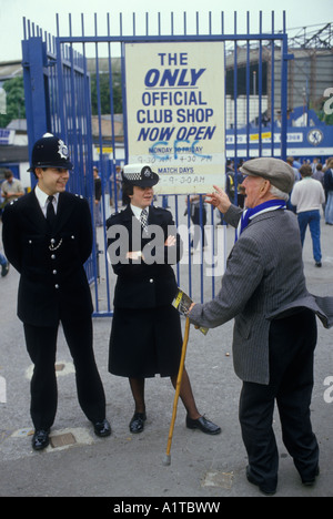 Chelsea Football fan talking a policeman and policewoman on crowd controle duty at the   Stamford Bridge London - Stock Photo