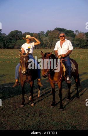 tourists, adult man, adult woman, guided tour, horseback ride, Caiman Ecological Refuge, Pantanal, Mato Grosso do - Stock Photo