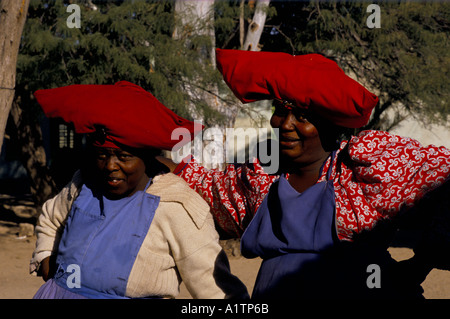 TWO HERERO WOMEN WEARING LARGE RED HATS NAMIBIA - Stock Photo