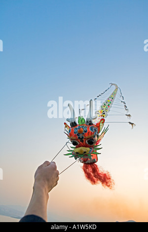 CHINA YANGTZE RIVER Chinese dragon kite flying from Yangtze River cruise ship during party at sunset on top deck - Stock Photo