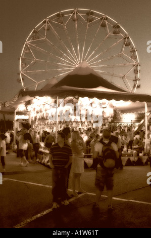 Moody sepia toned view of teenagers on carnival midway near Ferris wheel San Diego County Fair Del Mar California - Stock Photo
