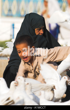 AFGHANISTAN Mazar I Sharif Shrine of Hazrat Ali Boy chasing famous white pigeons with his mother - Stock Photo