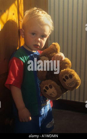 Little Boy Holding One Of His Teddy Bears - Stock Photo