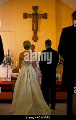 BRIDE and GROOM STAND TOGETHER BEFORE THE PRIEST TO TAKE THEIR VOWS DURING ROMAN CATHOLIC WEDDING - Stock Photo