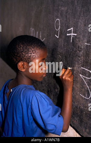 RWANDA KIGALI PRIMARY SCHOOL.Young girl writing on blackboard with chalk. 1995 - Stock Photo