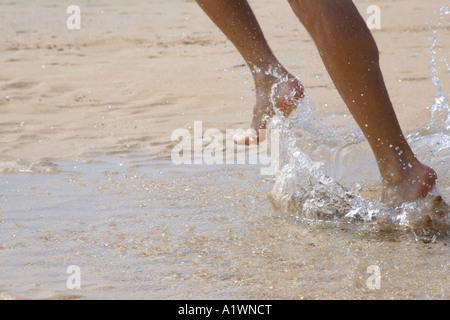 Man running through water at beach, England, UK - Stock Photo