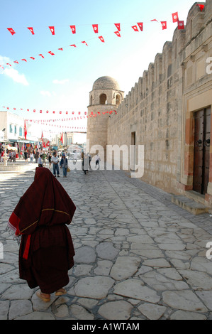 Bazaar on the medina of Sousse city in Tunisia. Old tunisian woman in traditional covered dress walking next to - Stock Photo