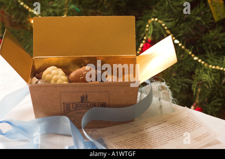 An open box of assorted handmade Belgian chocolates in front of a decorated Christmas tree - Stock Photo