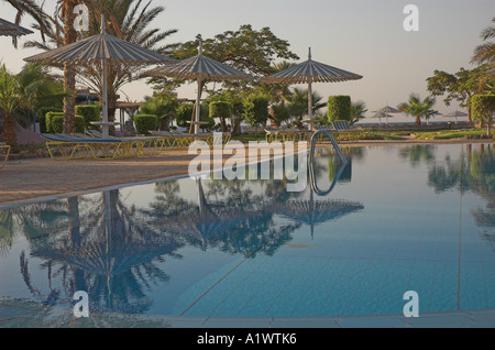 Deserted hotel swimming pool in the earling morning sunrise in Nuweiba Egypt - Stock Photo