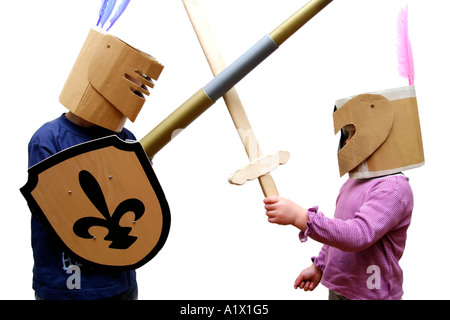 boy aged 5 and girl aged 2 pretending to be knights in armour with homemade cardboard helmets - Stock Photo