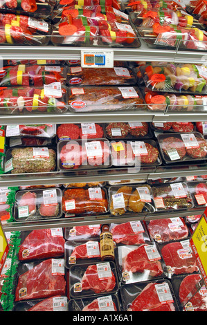 A meat case in a supermarket with fresh meats and beef steaks wrapped for sale - Stock Photo
