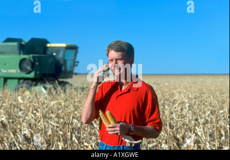 Farmer talks on wireless phone during corn harvest in Colorado,  USA - Stock Photo