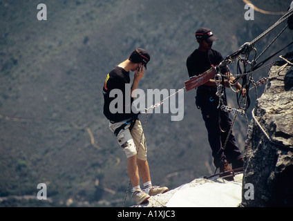 Young man using mobile phone at top of abseil from 'Table Mountain' near upper cable station Cape Town Western Cape - Stock Photo