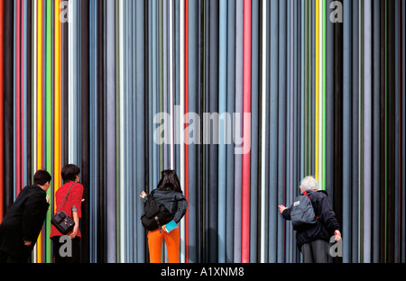 People touching the 'Cheminee d'Aeration' at La Defense, Paris, France. - Stock Photo