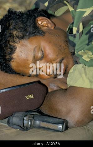 ANGOLA CIVIL WAR AUG 1993 SOLDIER ASLEEP WITH HIS GUN NEXT TO HIM - Stock Photo