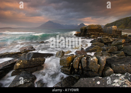 Fiery sunrise lights up the clouds over a raging Scottish sea, Elgol, Isle of Skye - Stock Photo