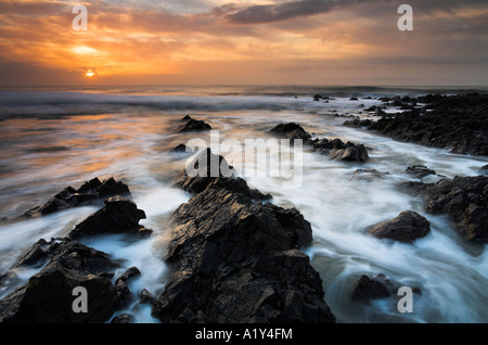 High tide at sunrise at Port Eynon in the Gower Peninsula, Wales - Stock Photo