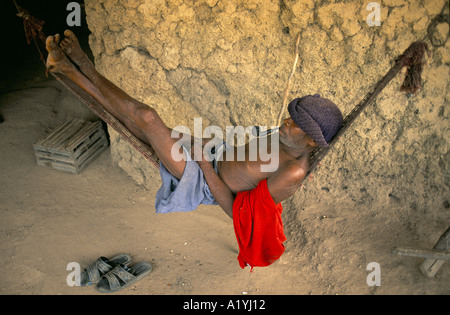 SIERRA LEONE 1996 ELDERLY MAN LYING ON A HAMMOCK SMOKING A PIPE DISPLACED PEOPLE BY THE WAR CAMP IN BO TOWN 1996 - Stock Photo