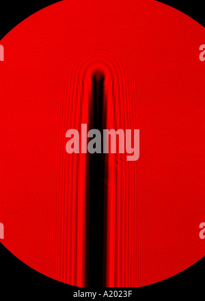 diffraction of red helium-neon laser light round the tip of a needle - Stock Photo