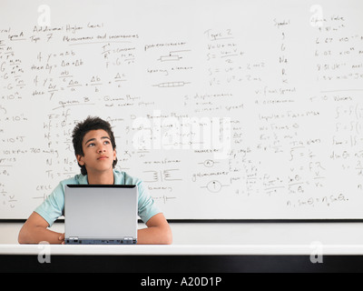 Teenage boy sitting in front of whiteboard in classroom - Stock Photo
