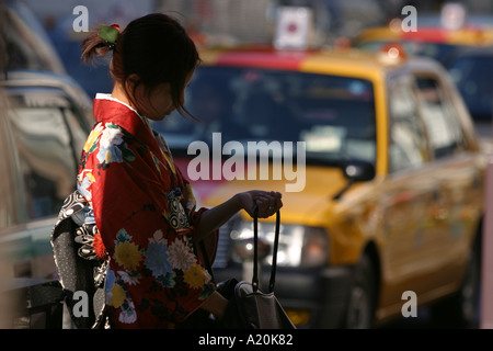 A girl wearing a kimono in the street with taxi behind her in the upmarket shopping district of Ginza, Tokyo, Japan - Stock Photo