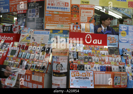 Mobile telephones with various providers Vodafone NTT DoCoMo Au all compete in the stall of an electronics store, - Stock Photo