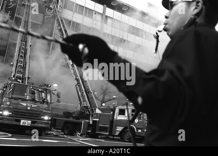 policeman holds a rope to control crowds watching a fire in Akihabara Electric Town district of Tokyo, Japan - Stock Photo